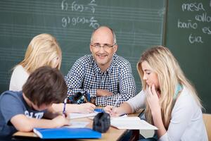 Motivated male teacher with his students sitting at a table together in a group discussion-1